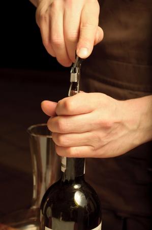 A sommelier opening wine bottle for blind winetasting