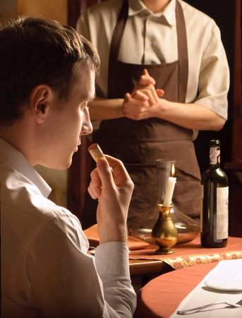 A young man sniffing the cork of a wine bottle photo