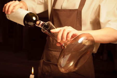 A sommelier pouring red wine into decantor photo