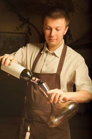 A sommelier pouring red wine into decanter photo