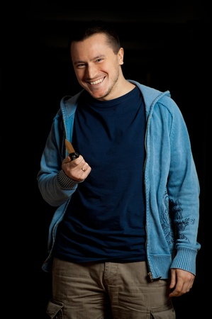 Smiling man holding knife - aggression photo