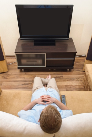 Man lying on sofa watching TV at home. photo
