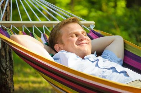 in hammock: Young man sleeping in a hammock
