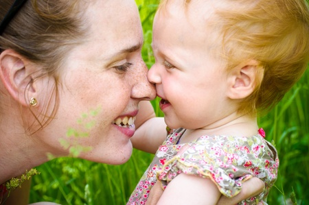Portrait of mother and her little baby playing - outdoors