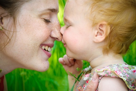 Portrait of mother and her little baby playing - outdoors photo