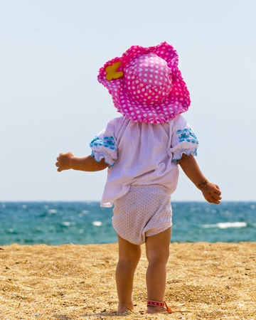 toddler walking: Cute baby girl playing on the beach