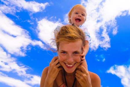 Smiling baby with her mother on the beach photo