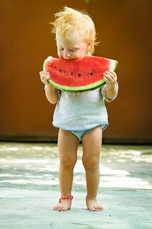 Cute infant baby with a delicious melon photo
