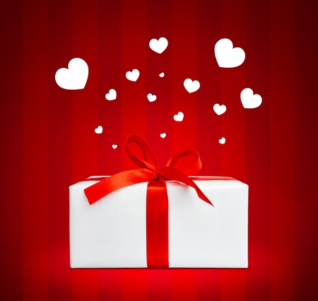 Present box with red ribbon. Small hearts flying over it. photo