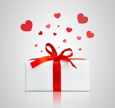 Present box with red ribbon. Small hearts flying over it. Stock Photo - 10668041