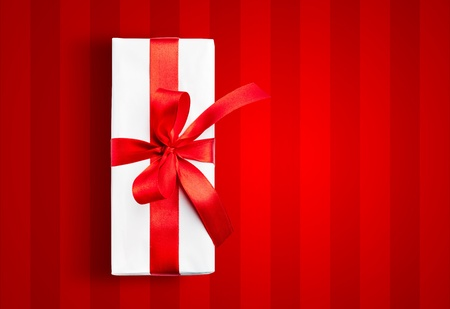 White box with a red ribbon on stripped background Stock Photo - 10668038