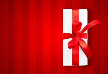 White box with a red ribbon on stripped background photo