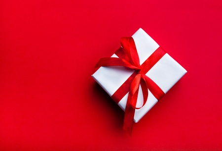 Small gift with red bow on red background. Free space for your text. Stock Photo