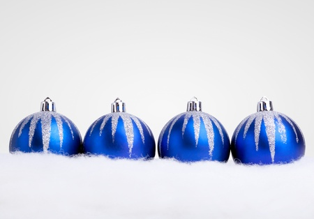 four objects: Glittering blue christmas balls on white  background. Copy space for your text.
