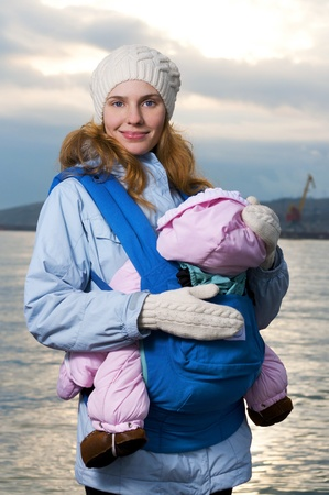 Lifestyle portrait of young mother and baby outdoor photo