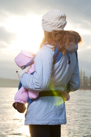 baby carrier: Lifestyle portrait of young mother and baby outdoor Stock Photo