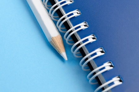 White pencil and spiral of notebook - macro photo