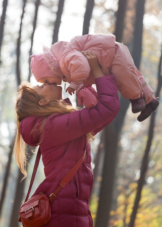 Cute little baby with mother in park playing photo