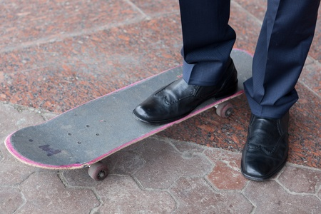 Closeup of businessman standing on skateboard photo