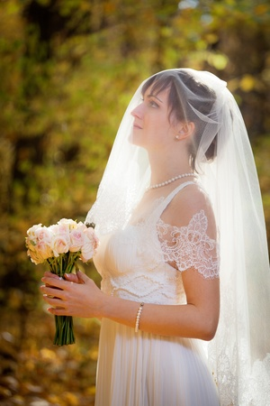 wedding veil: Beautiful Bride with wedding bouquet in the park