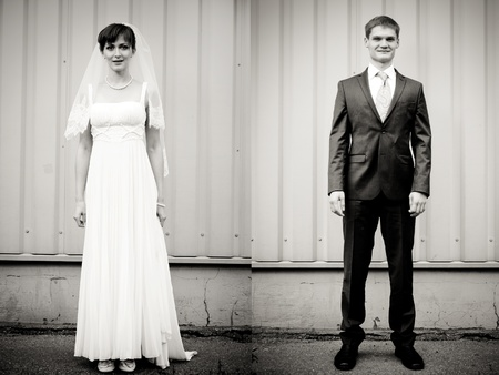 Full Lenght portrait of bride and groom standing against wall photo