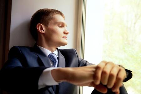 nerveux: Jeune homme assis sur rebord de fenêtre - mariée en attente