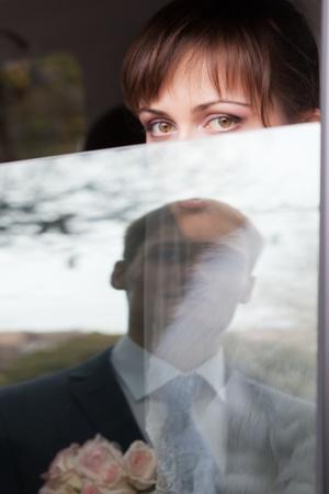 Bride looking trough car window - concept photo