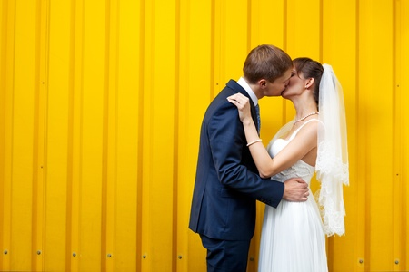 Bride and groom kissing against yellow wall photo