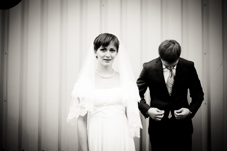 Portrait of bride and groom standing against wall photo