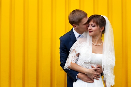 Happy Bride and groom against yellow wall photo
