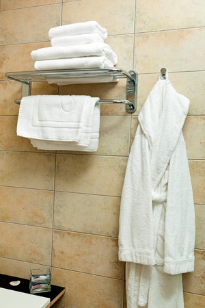 clothes rail: This is a closeup of a towels and bathrobes