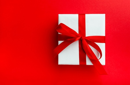 Small gift with red bow on red background. Space for your text. photo