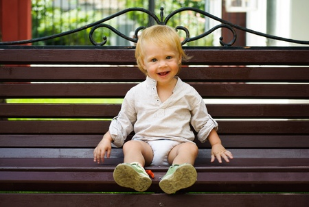 Cute little baby sitting on bench - outdoor photo
