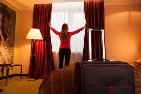 opening window: Mujer joven en una ventana de apertura de hotel Foto de archivo