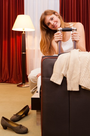 Smiling young woman sitting in hotel room photo