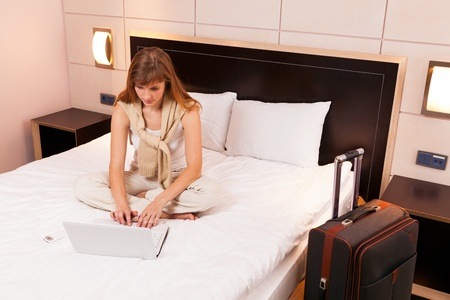 Young woman using laptop in a hotel bedroom Stock Photo - 12935305