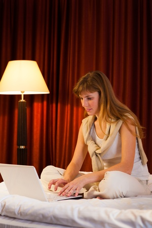 Young woman using laptop in a hotel bedroom photo