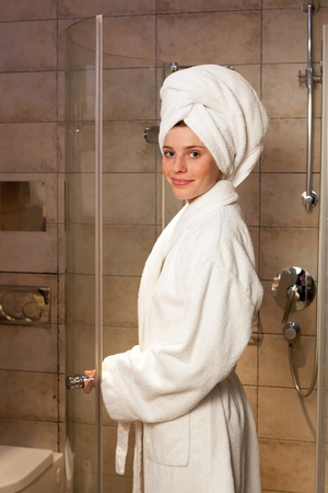woman bathrobe: Young woman wearing a white robe in the hotel