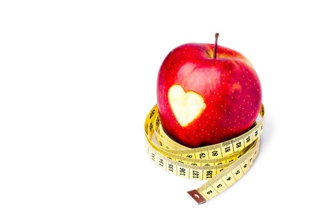 Red apple with a heart symbol against white background photo