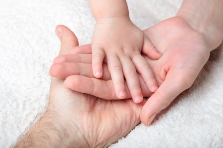 papa y mama: Primer plano de la mano del beb� en las manos de la madre y el padre Foto de archivo