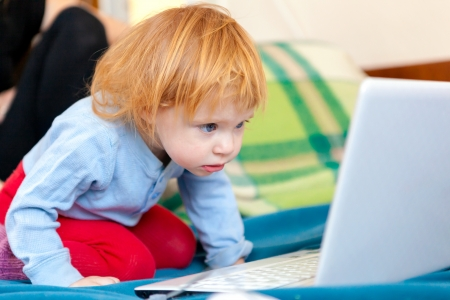 Little bright girl with laptop at home