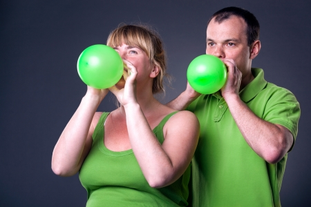 inflating: Happy young couple having fun with balloons - studio shot