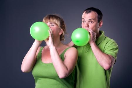 Happy young couple having fun with balloons - studio shot Stock Photo - 15038476