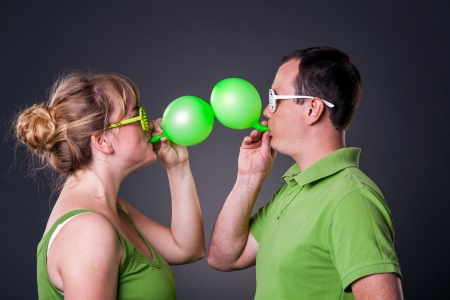Happy young couple having fun with balloons - studio shot Stock Photo - 15038452
