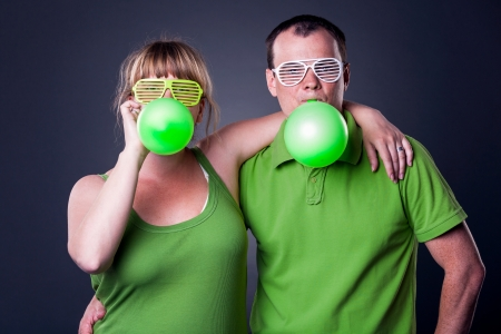 Happy young couple having fun with balloons - studio shot Stock Photo - 15038482