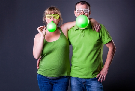 Happy young couple having fun with balloons - studio shot Stock Photo - 15038487
