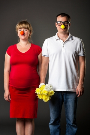Portrait of funny couple with funny noses and bunch of flowers photo