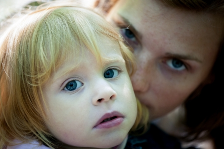 sad eyes: Sad portrait of mother and daughter - outdoor Stock Photo