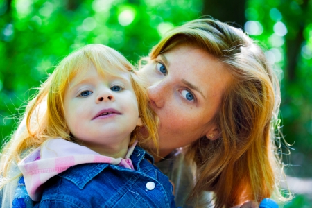 Mother playing with her daughter - outdoor shot photo