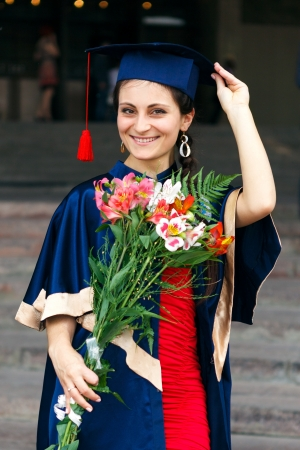 Image of a happy young graduate with flowers photo